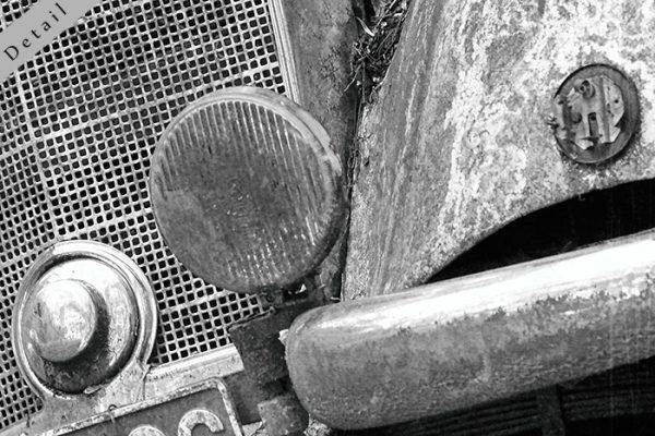 Hier sieht man einen Bildausschnitt 4 mit Kotflügel, Stossstange und Scheinwerfer, schwarz weiss, vintage.