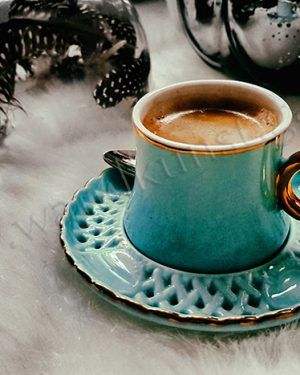 Die Tasse Mokka mit Gold. Eine lecker gefüllte Espressotasse mit goldenen Henkel steht auf flauschiger Tischdecke.