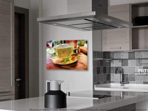 Cafe Color - buntes Gold. Hier sieht man ein farbenfrohes Wandbild aus Papier mit Metallic Effekt in der Küche hängend. Das Motiv ist eine Kaffeetasse aus Porzellan, gefüllt mit Milchkaffee und Schaum -mit einem Löffel und einer Tüte Zucker.