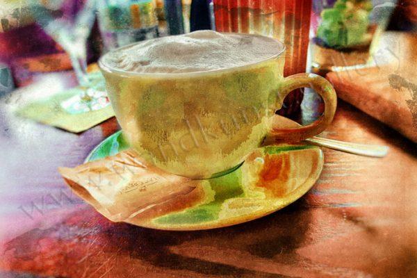 Cafe Color - buntes Gold. Hier sieht man ein farbenfrohes Wandbild aus Papier mit Metallic Effekt. Das Motiv ist eine Kaffeetasse aus Porzellan, gefüllt mit Milchkaffee und Schaum -mit einem Löffel und einer Tüte Zucker.