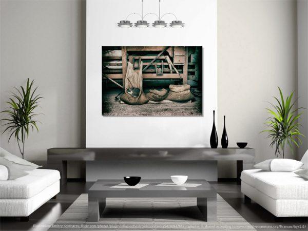 Hier sieht man ein grosses Wandbild im Wohnzimmer an der Wand hängend. Das Motiv ist eine Katze im Sack, schlafende Fellnase in der Natur.