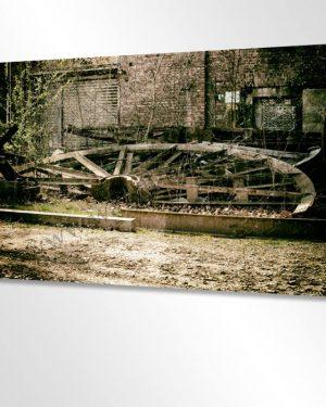 Hier sieht man einen Ausschnitt von einem grossen Wandbild aus gebürstetem Leichtmetall im Schlafzimmer hängend. Das Bild zeigt eine urbane Industrie vergangener Zeit, das demontierte Rad eines Förderturms. Urban Art Wandbild mit Vintage Look.