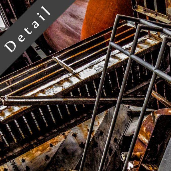 Der alte Maschinenraum mit Zahnrad - Kunst und Industrie im Wohnzimmer. Ausschnitt einer Wandekoration im XXL Format. Die künstlerische Seite gewesener Produktionsstätten der Schwerindustrie am Beispiel eines Hochofens.