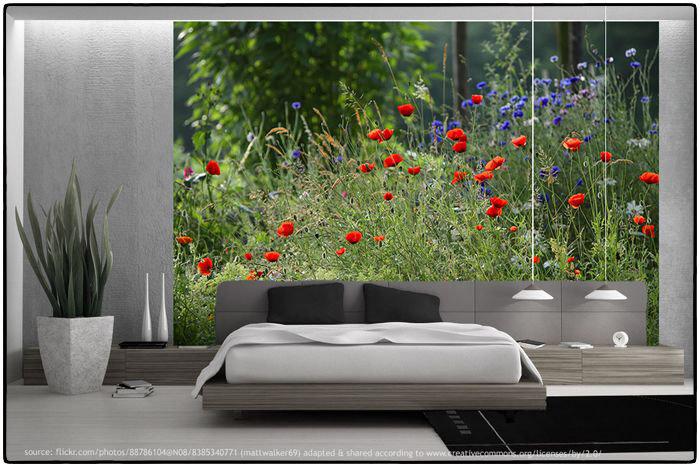 Geht nicht? Gibt es nicht! Schlafzimmer mit Wanddeko in Maßanfertigung. Über dem Bett hängt ein Wandpaneel im XXL Format an der Wand mit einer blühenden Wiese aus rotem Mohn.