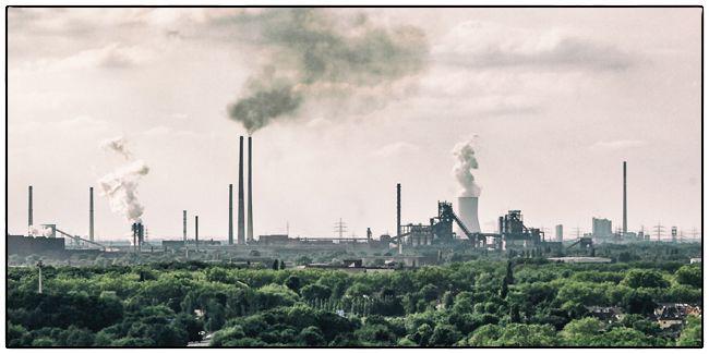 Dieses Bild zeigt den Horizont einer Industrielandschaft mit rauchenden Schornsteinen, Zechen und Hochöfen im Ruhrgebiet.