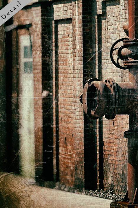 Hier sieht man einen Ausschnitt von einem grossen Wandbild aus gebürstetem Leichtmetall im Schlafzimmer hängend. Das Bild zeigt eine alte Fabrik, an der Wand aus Backstein laufen rostige Rohre entlang. Ein urbanes Wandbild mit Vintage Art.