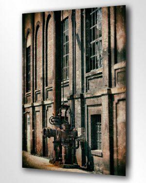 Hier sieht man ein grosses Wandbild aus gebürstetem Leichtmetall im Schlafzimmer hängend. Das Bild zeigt eine alte Fabrik, an der Wand aus Backstein laufen rostige Rohre entlang. Ein urbanes Wandbild mit Vintage Art.