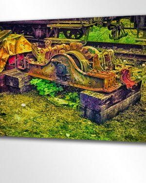 Bunte Maschinerie der Eisenbahn. Ausgediente Getriebeteile einer alten Lokomotive auf einem Betriebshof der alten Schmalspureisenbahn.