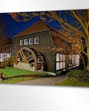 Ein Mühlrad am alten Fachwerkhaus hinter dem knorrigen Baum bei Nacht. Romantisches Relikt aus der guten alten Zeit.